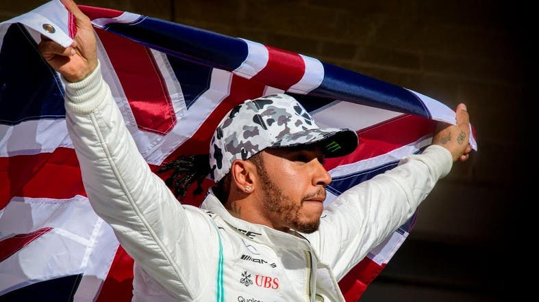 Mercedes AMG Petronas Motorsport driver Lewis Hamilton (44) of Great Britain holds up the Union Jack as he celebrates winning his sixth world championship. (Reuters)